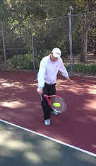 Client in training session hitting tennis ball with racket
